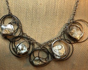 Multi wire circles on rope silver tone chain necklace with shell