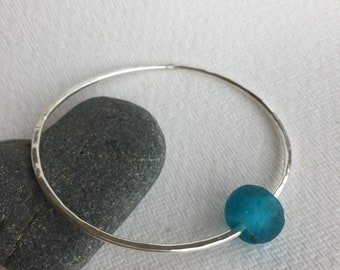 Silver bangle with a blue recycled glass bead