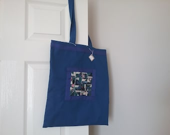 Blue tote bag with patchwork embroidered panel
