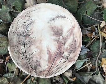 Very earthy hand-made bowl with details of prairie plants embedded in the clay.  Both sides decorated.
