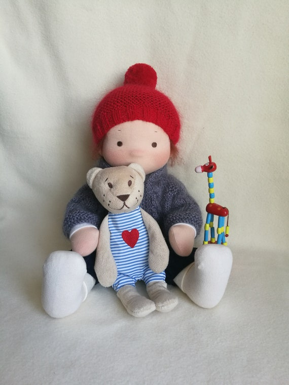 Textile doll with a set of clothes