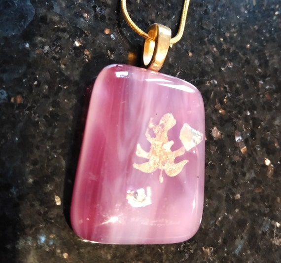 Glass fused anime creature pendant on dark pink.