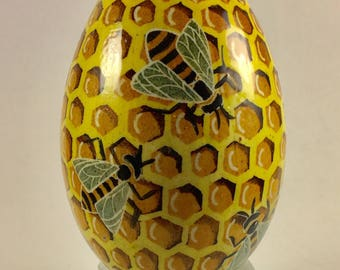 Colorful goose egg pysanka, decorated with images of sunflowers, honeycomb and bees in yellows and turquoises