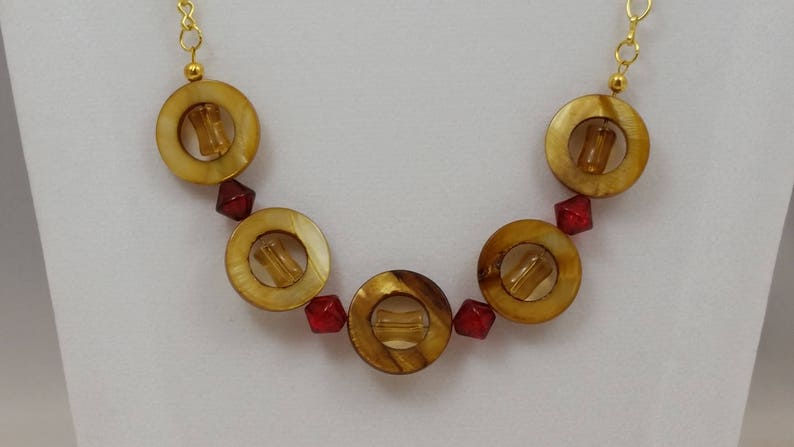 Gold shell donuts surround amber beads with red glass bicones on gold chain