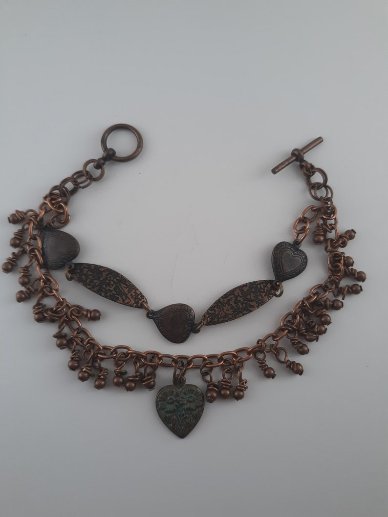 Copper charm bracelet with hearts and textured links and copper beads