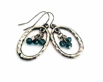Gold hammered look hoop earrings with dangling blue/emerald crystals. Free shipping within the USA.