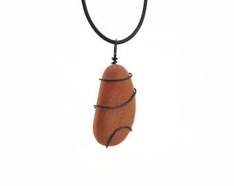 Natural stone worn as a pendant on a strip of leather or at the neck on a hoop