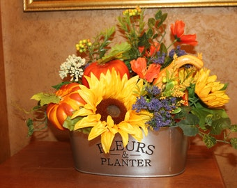 Beautiful fall arrangement with pumpkins and gourds and florals in a tin container.