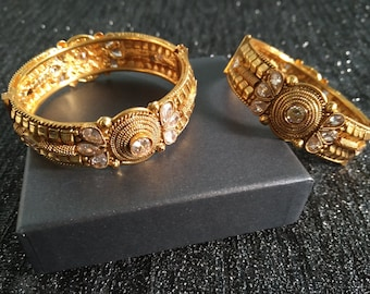 bangle with carefully crafted with stones in green and red colour kada comes in a set of four gold sleek bangle