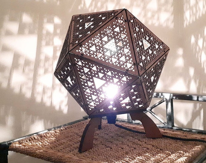 Wooden table lamp to lay in platonic shape with projection of geometric shapes in fractal Sierpiski laser cutting
