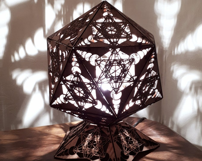 Wooden table lamp to be laid in platonic shape with projection of laser-cut metatron shapes.