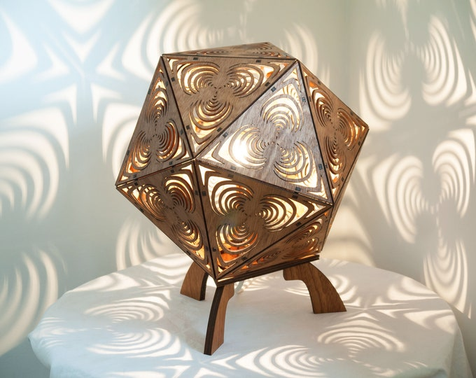A wooden table lamp to be placed in a platonic shape with projection of geometric shapes in spirals cut by laser.