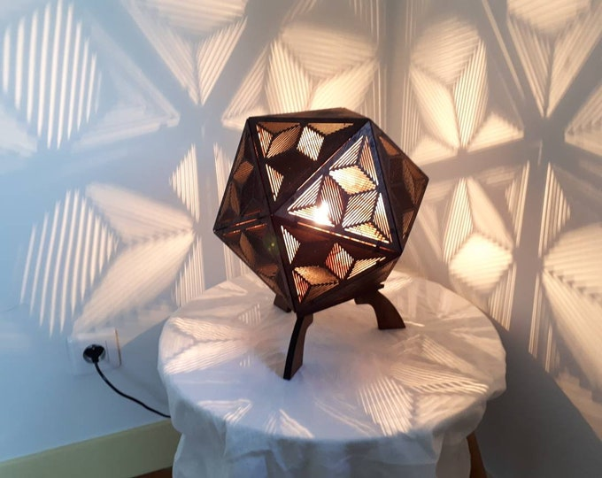 Wooden lamp to lay, bedside lamp platonic shape icosahedron, optical illusion drawing with projection of shadows. Laser cutting.