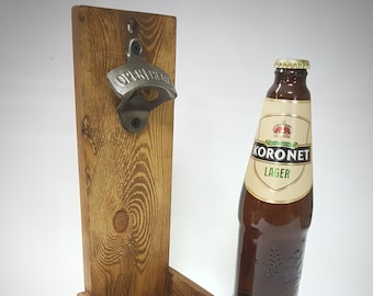 Wall mounted bottle opener with cap catcher.