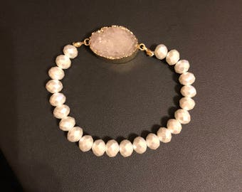 White druzy geode stone wrapped in golden foil on an elastic bracelet with white faceted beads.