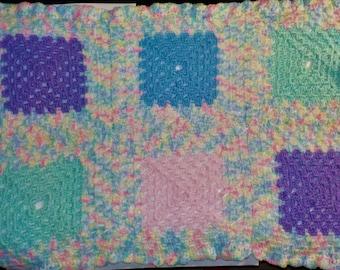 Crochet granny square crib-sized baby blanket