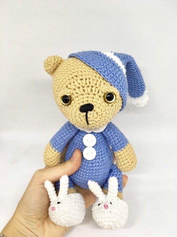 Small knitted teddy bear in pajamas and a sleeping cap is sleeping ... | 761x570