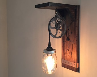 Rustic Steampunk wall light with barn wood, mason jar, pulley and Edison bulb and a shelf. Cool lighting. Farmhouse or steampunk style