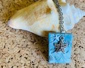 Silver-blue beach motif n...