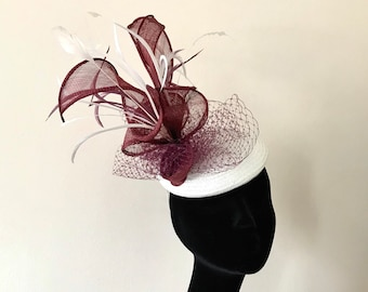 fascinator/ hat with a white straw base and sinamay decoration in burgundy colour