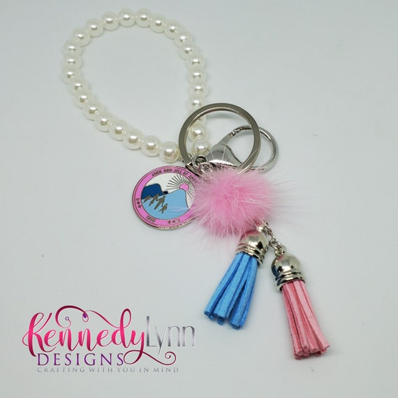 Jack and Jill of America, Inc. pearl charm key chain with pom and tassel embellishment