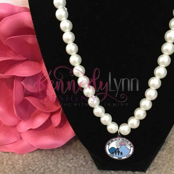 Faux pearl necklace with Jack and Jill emblem charm
