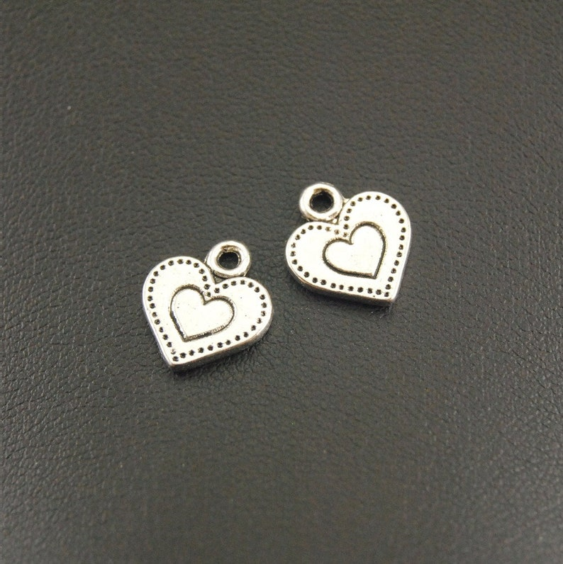 50 x TIBETAN STYLE ANTIQUE SILVER HEART WITH WING CHARMS 13mm x 12mm