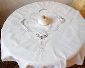 A vintage white cotton tablecloth. Madeira embroidery and crocheted crochet. The antique tablecloth is a gift from the mother.