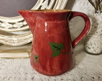 Maroon pitcher with green leaves