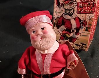 "Mechanical Long-Neck ""The Santa Claus"", original box. Santa stands 6 1/2"" Tall, Red Suit , White Trim, Black Belt. Hand Painted Plastic Head"