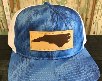 d6f4c6bd North Carolina Leather Patch NC Trucker Hat Realtree Fishing Camo/White