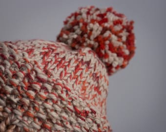 Three-coloured wool cap with hand-knitted pompom with two needles.