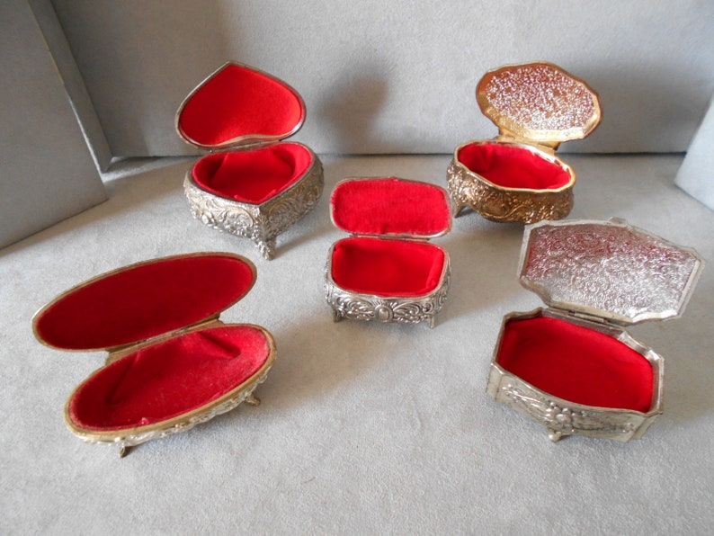 set of 8 boxes and box has jewels inside padded velvet red and blue