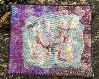 "Table mat, hand dyed, felted, and quilted, 12.5"" by 15""."