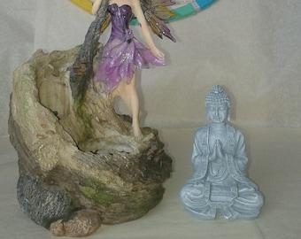 Grey Buddha in prayer or meditation position