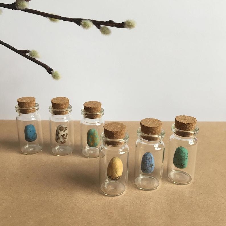 little handmade eggs hanging in small glass bottles