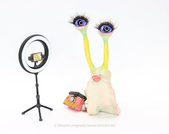 Influencer snail with ring light and handbag, polymer clay figure as decoration, artificial figure with character, homorvolle snail figure