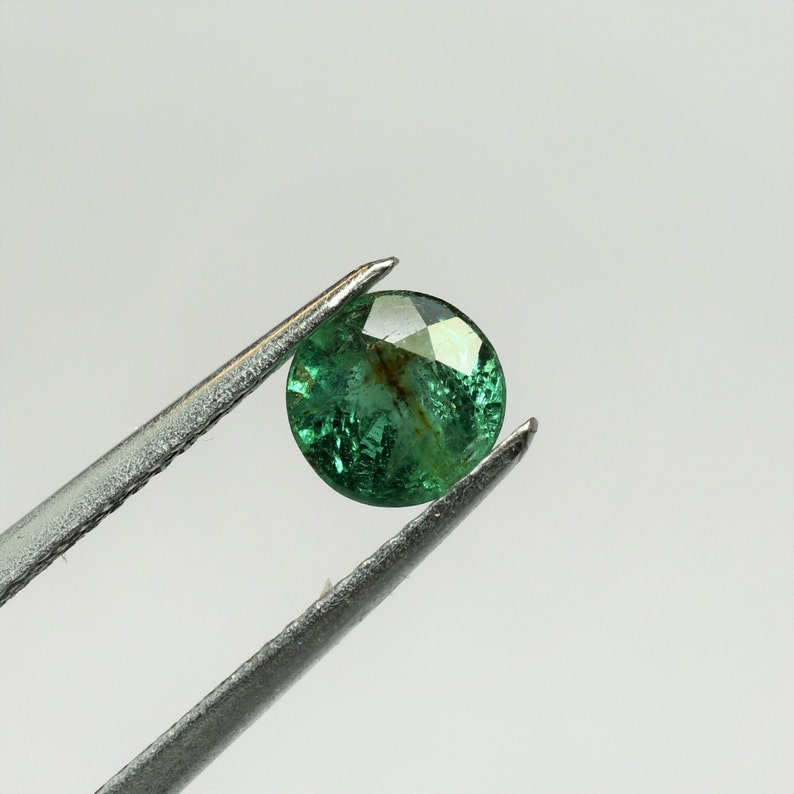 Untreated this 6 mm round beryl weighs 0.75 carats undeded natural emerald from Zambia