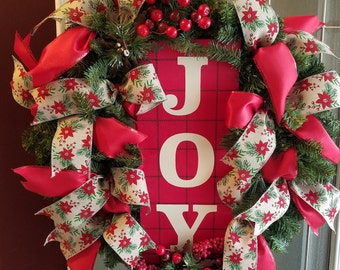 """24"""" artificial evergreen wreath with red and green ribbon. Metal snowflake decor with cranberries and greenery. Wooden sign"""