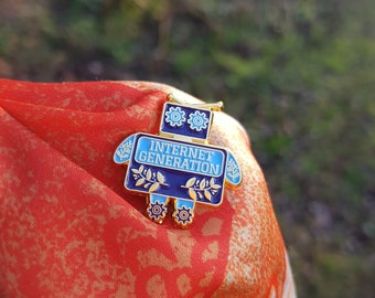 Internet Generation pin - a blue and gold enamel pin of a robot, celebrating internet culture and sci fi