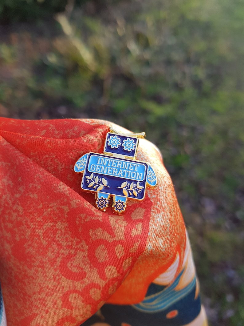 Internet Generation pin  a blue and gold enamel pin of a image 0
