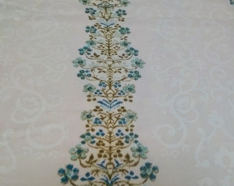 Columns of tiny blue flowers between white curling design on cream cotton polyester blend
