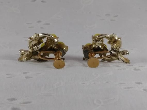 Dark gray moon glow screw back earrings in gold tone metal from the 1960s