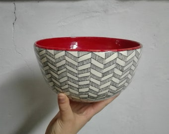 Handmade ceramic bowl made and decorated by hand with black geometries on white background and red interior
