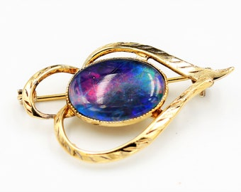 Silver gilt brooch with black opal-like oval mounted cabochon