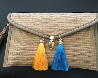 Straw clutch with hanging tassels. Can be used as a clutch or with a wristlet or with a leather strap.