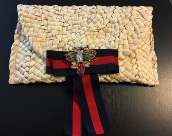 Straw bag with red and navy hanging bow with bumblebee detail