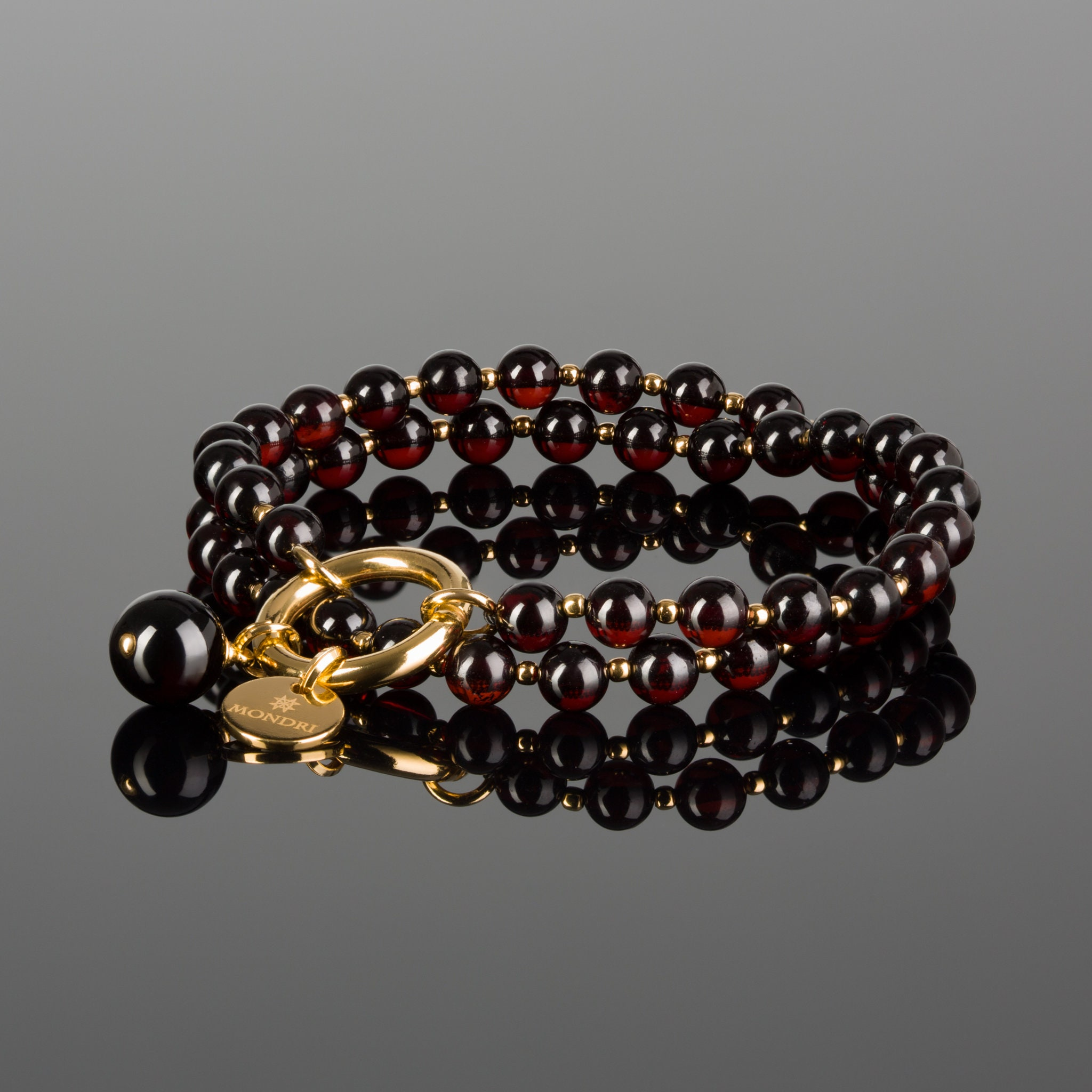 Red baltic amber and gold plated sterling silver charm bracelet
