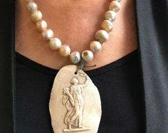 Pearl necklace with a terracotta medallion.