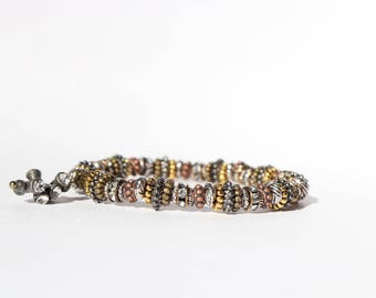 Beaded metal bracelet with charm